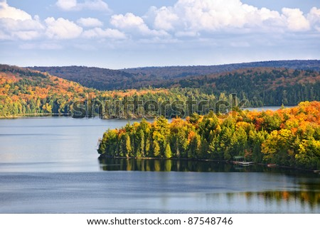 Fall forest of colorful autumn trees on islands in calm lake - stock photo