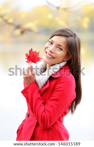 Fall girl holding red Autumn leave outside. Asian woman outdoor portrait in red seasonal autumn coat by fall forest lake. Female model smiling happy looking at camera. Mixed race Asian Caucasian girl. - stock photo