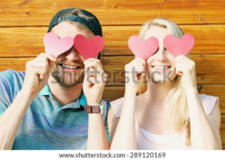 fall in love concept - young couple holding paper hearts over eyes - stock photo