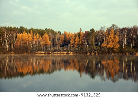 Fall in Tomahawk, Wisconsin. Colorful trees reflected in the lake. - stock photo