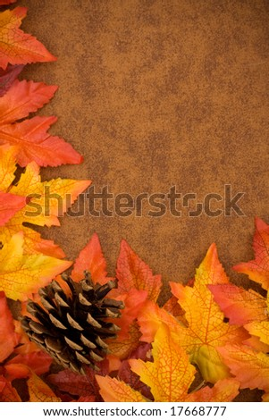 Fall leaves with a pinecone on brown background, fall border - stock photo