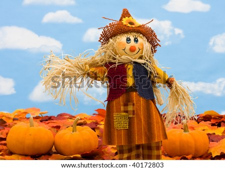 Fall leaves with a scarecrow and a gourd on a sky background, fall border - stock photo