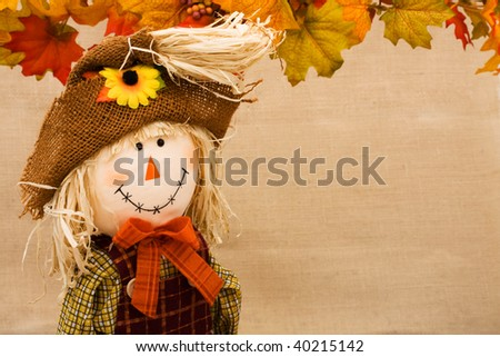 Fall leaves with a scarecrow making a border on a beige background, fall border - stock photo