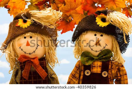 Fall leaves with a scarecrow  on a sky background, fall scene - stock photo