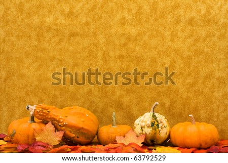Fall leaves with pumpkins and gourds on a brown background, Fall Scene - stock photo