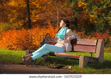 Fall lifestyle concept, harmony freedom. Casual young woman girl relaxing in autumnal park sitting on bench with book having fun, closed eyes. Golden colorful leaves background