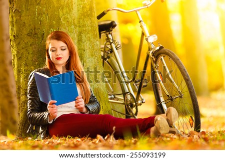 Fall lifestyle concept. Redhaired young woman girl relaxing in autumn park reading book, sitting alone under tree. Sunny day - stock photo