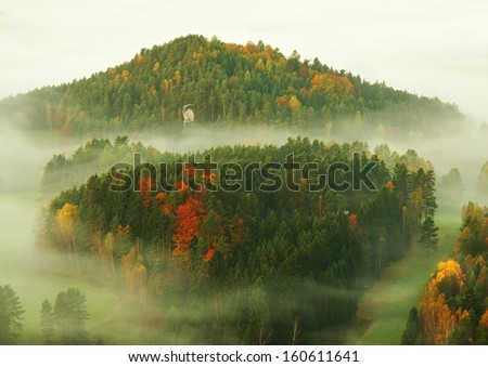 Fall misty valley early morning within sunrise. The fog is moving between hills and peaks of trees a makes with sun rays gentle reflections. Wonderful autumn morning in Bohemian Switzerland. - stock photo