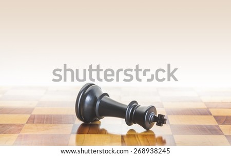 Fall of the chess king, metaphor or concept for loss, defeat or surrender - stock photo