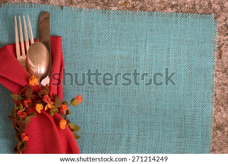 Fall or Summer Table Placesetting above view with Cloth Napkin, Fork, Knife, Spoon, Flower Ring on Cyan Burlap Mat on Stone Table with room or space for copy, text,  words.  Horizontal looking down - stock photo