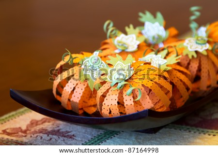 Fall pumpkin centerpiece crafted out of folded and stamped paper.