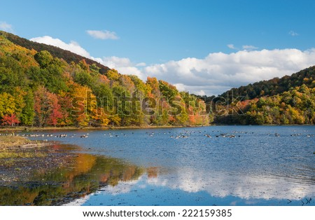 Fall reflections in the peaceful Hertel Lake, Mont Saint Hilaire, Quebec, Canada - stock photo