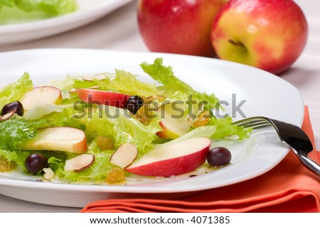 Fall salad with apples, almonds, raisins  and black olives served for healthy lunch