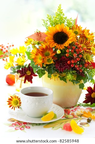 fall still life with cup of tea and autumnal flowers - stock photo