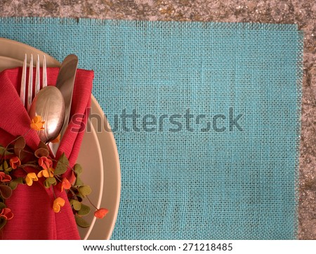 Fall, Summer Placesetting above view with tan plates, fork, knife, spoon, napkin, ring, on cyan burlap placemat on stone table with room or space for copy, text, words.  Horizontal looking down  - stock photo