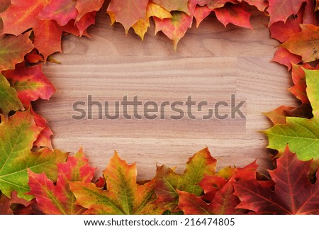 Fall-themed border of autumnal maple leaves around a walnut wood background - stock photo