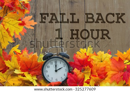 Fall Time Change, Autumn Leaves and Alarm Clock with grunge wood with text Fall Back 1 Hour - stock photo
