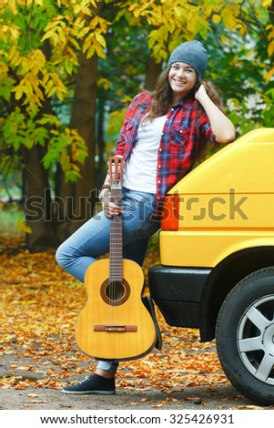 Fall time full length portrait of cheerful guitarist girl is travelling by yellow van - stock photo
