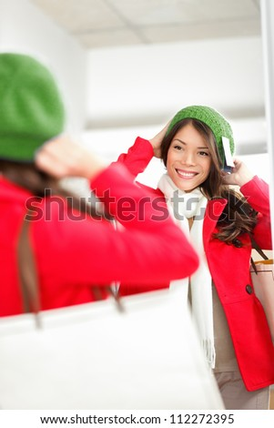 Fall / Winter shopping woman trying on knit hat looking in mirror smiling happy holding shopping bags inside in clothing store. Multiracial shopper woman.