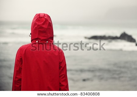 Fall woman in rain looking at ocean on grey day. - stock photo