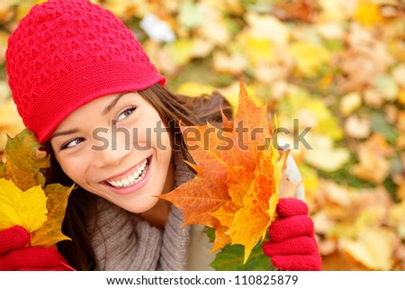 Fall woman looking at copy space holding fall leaves smiling happy and joyful. Lovely beautiful girl wearing red knit hat and gloves. Fall lifestyle concept image. - stock photo