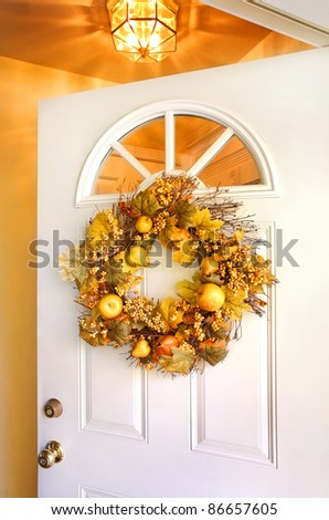 Fall wreath on an open door - stock photo