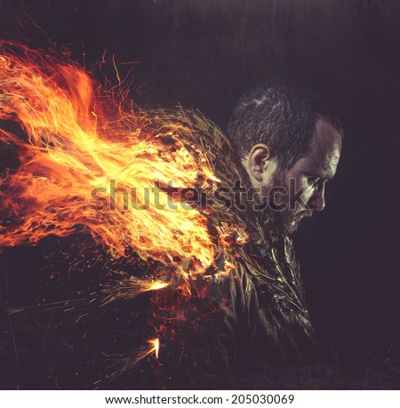 fallen angel, jacket man with golden feathers on the wings and fire - stock photo