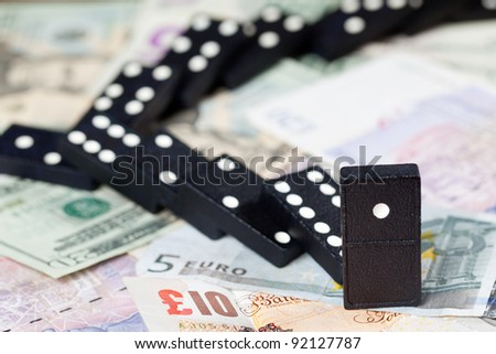 Fallen dominoes on pound, euro and dollar bank notes illustrating banking crisis or Brexit - stock photo