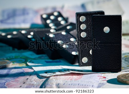 Fallen dominoes with blue harsh shadows on pound, euro and dollar bank notes illustrating banking crisis or Brexit - stock photo