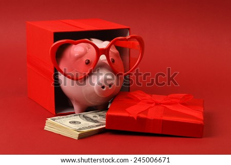 Fallen in love piggy bank with red heart sunglasses standing in gift box with ribbon and with stack of money american hundred dollar bills on red background - stock photo