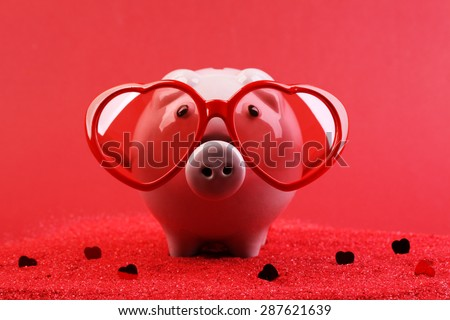 Fallen in love piggy bank with red heart sunglasses standing on red sand with red shining heart glitters in front of red background - stock photo