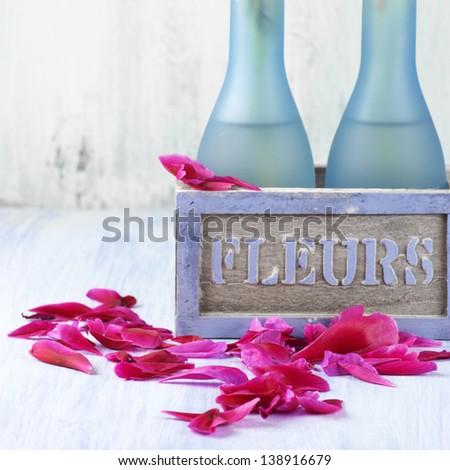 Fallen peony petals around rustic flowerpot. - stock photo