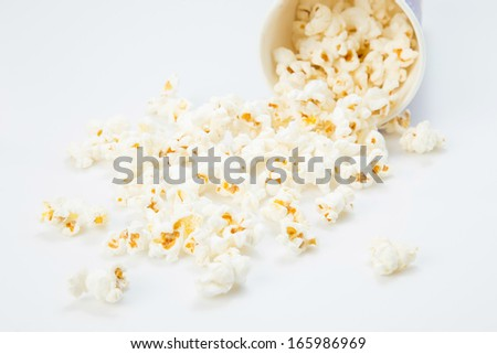 fallen popcorn in box on white background - stock photo