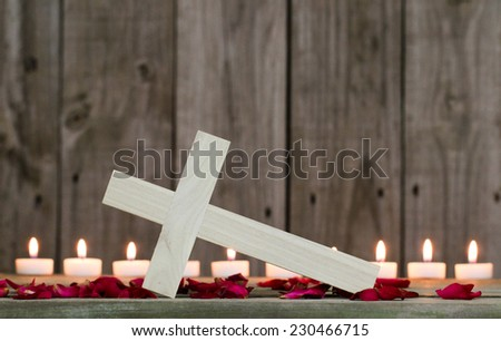 Fallen wooden cross by burning candles and rose petals with rustic wood background - stock photo