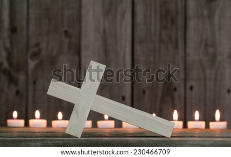 Fallen wooden cross by candlelight with rugged wood background - stock photo