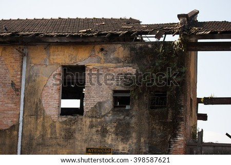 Falling apart old brick house with plants on wall - stock photo