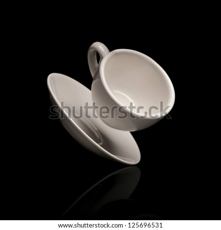 falling coffee cup with saucer isolated on black background - stock photo
