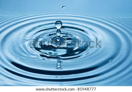 Falling Drop of water on blue. - stock photo