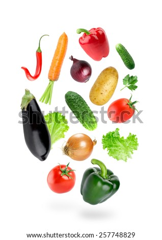 Falling fresh color vegetables on white background - stock photo