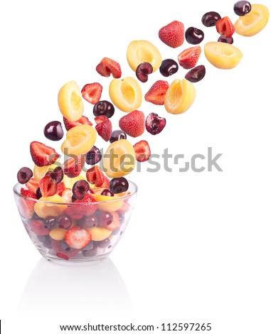 Falling fruit in a glass bowl. Isolated on white. - stock photo
