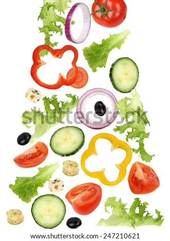Falling green salad with tomatoes, Feta cheese, onion, olives and cucumber - stock photo