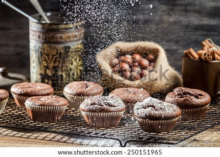Falling icing sugar on fresh chocolate muffins - stock photo