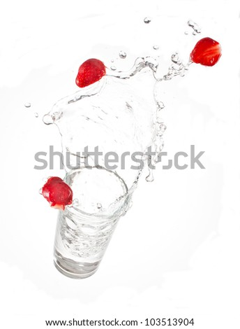 falling red ripe strawberry with glass of water with splash