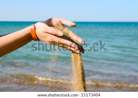 Falling sand in woman hands over sea