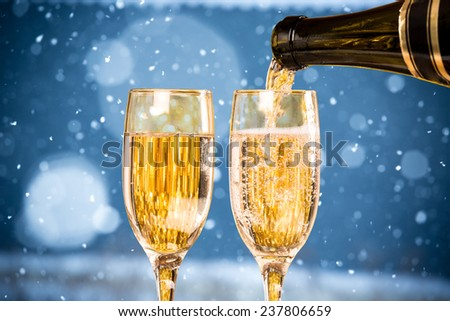 Falling Snow with Two Champagne Glasses On The Blue Background