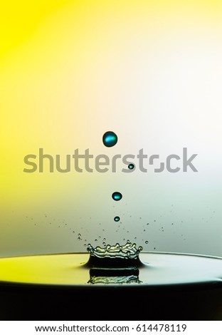 Falling water drop close up image with a yellow background.