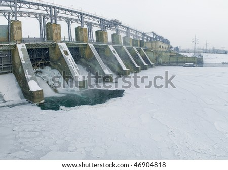 falling water, snow and ice plate at a river in cold winter - stock photo