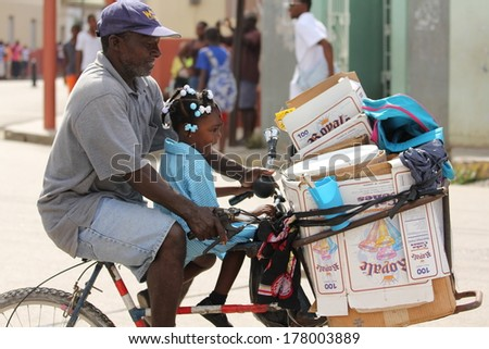 FALMOUTH, JAMAICA � MAY 11: An unidentified man with daughter riding bicycle outside the port of Falmouth on MAY 11, 2011 in Jamaica ahead of the national labour day celebrations. - stock photo