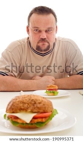 False advertising and reality - man unhappy about the size of his hamburger - stock photo