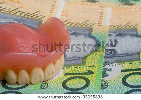 false teeth prosthetic on australian dollar bills with focus on the front teeth - stock photo